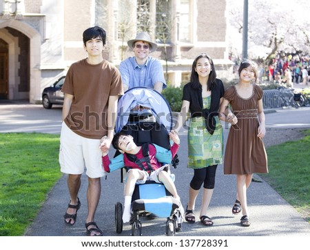 Father walking with his biracial children outdoors. Disabled son in wheelchair has cerebral palsy. - stock photo