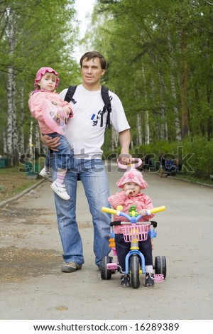 Father walking with their daughters along the way in a park: elder girl  is on his hands, younger ride on a tricycle