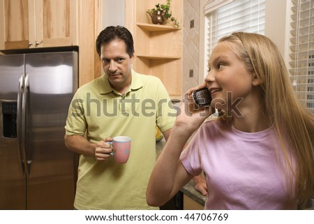 Father watching daughter talk on cell phone while in kitchen - stock photo
