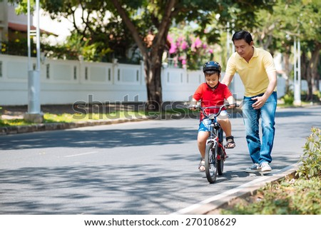 Father watching his son riding a bike - stock photo
