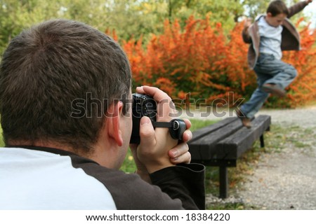 Father with a digital video camera recording his son. - stock photo
