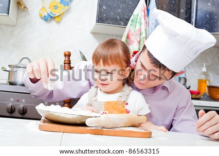 father with a small daughter do dough for pies