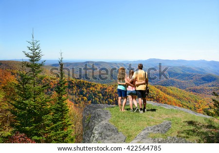 Father with arms around his daughter and wife looking at beautiful fall Blue Ridge Mountains landscape. Blue sky in the background. North Carolina, USA. - stock photo