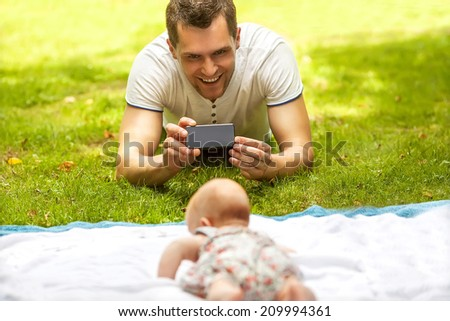 Father with baby In Park  taking selfie by mobile phone - stock photo