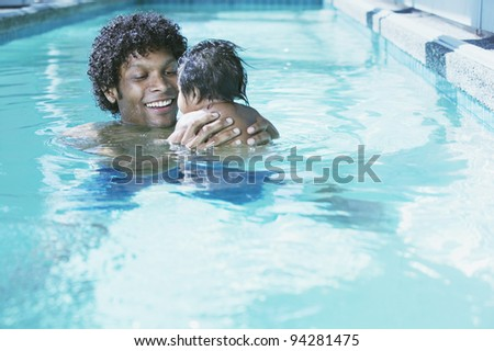 Father with baby in swimming pool - stock photo