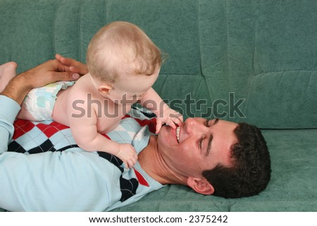 father with baby on sofa - stock photo