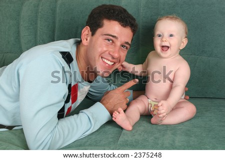 father with baby on sofa 2 - stock photo