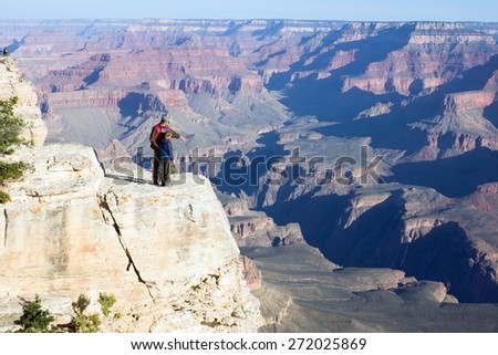 Father with child stand on a cliff. Adult explains how formed the Grand Canyon in Arizona - stock photo