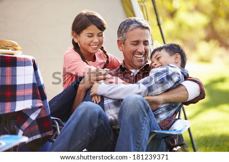 Father With Children Enjoying Camping Holiday In Countryside - stock photo