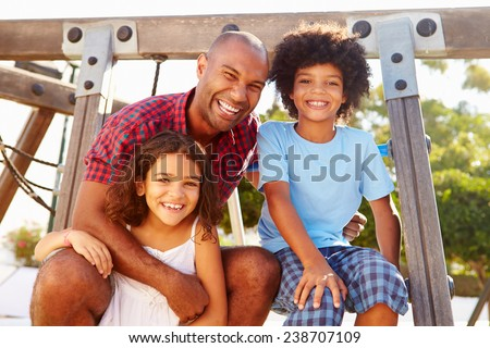 Father With Children On Playground Climbing Frame - stock photo