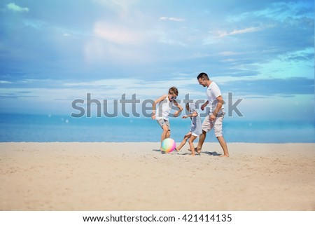 Father with children playing football on the beach at the day time. - stock photo
