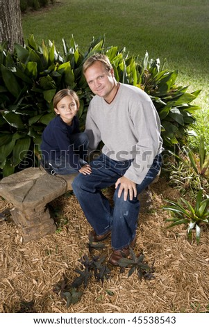 Father with cute little 5 year old boy sitting outdoors on bench - stock photo