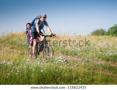 father with daughter cycling in summer - stock photo