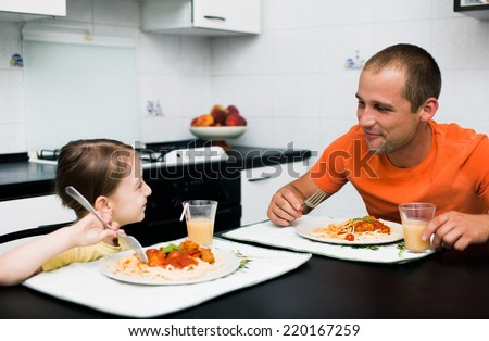 father with daughter eating pasta with sauce for the dinner - stock photo