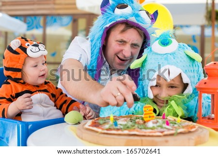 Father with daughter in monster costumes and baby boy in tiger costume celebrate the birthday in a cafe, father ignites candles.