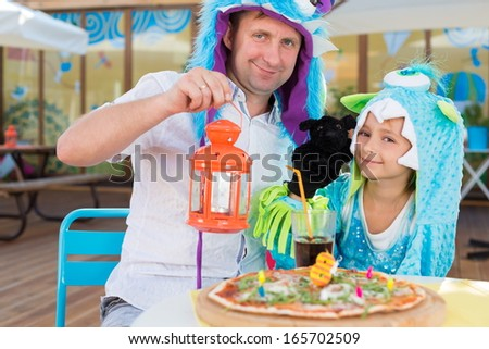 Father with daughter in monster costumes with dog toy celebrate the birthday in a cafe - stock photo