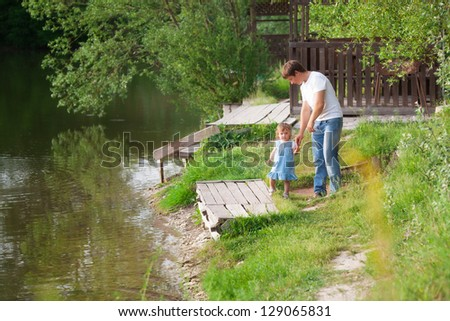 Father with daughter near the lake - stock photo
