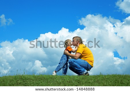 father with daughter on green grass under sky with clouds - stock photo