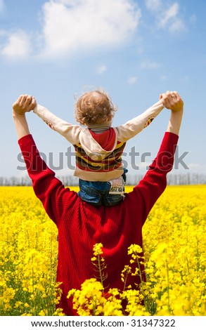 father with daughter on the rapeseed field