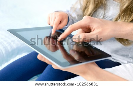 Father with daughter playing on digital tablet. Selective focus on the child's finger.