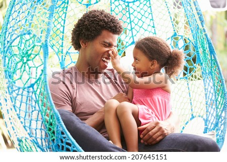 Father With Daughter Relaxing On Outdoor Garden Swing Seat - stock photo
