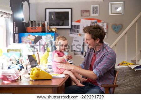 Father With Daughter Running Small Business From Home Office - stock photo
