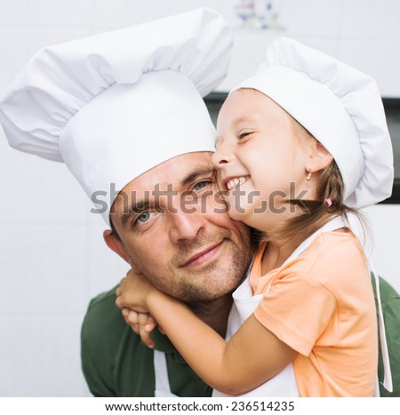 father with daughter  take some rolls on a baking tray  out of oven - stock photo