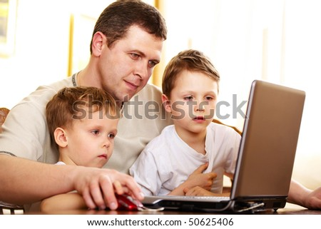 father with her children using laptop; shallow DOF, focus on closest boy's eyes