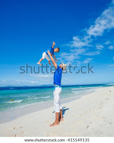 Father with her son having fun on beautiful sunny beach
