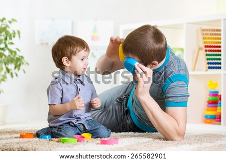 father with his child son play together at home - stock photo