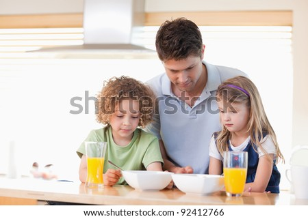 Father with his children having breakfast in their kitchen - stock photo