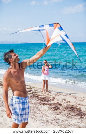 Father with his daughter kite flying outdoor coast ocean - stock photo