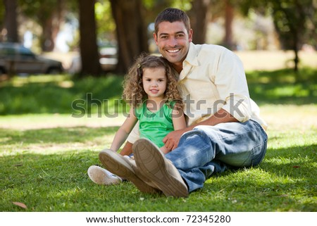 Father with his daughter sitting on the garden