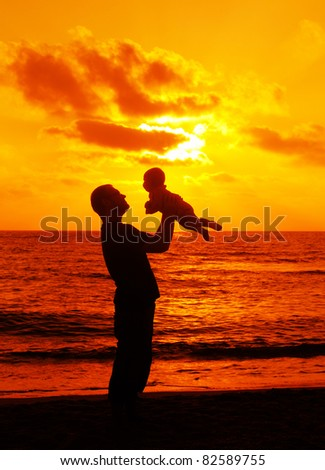 father with his little baby on the sea - stock photo