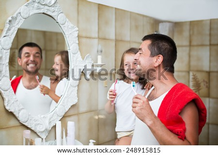 Father with his little daughter  brushing teeth in bathroom - stock photo