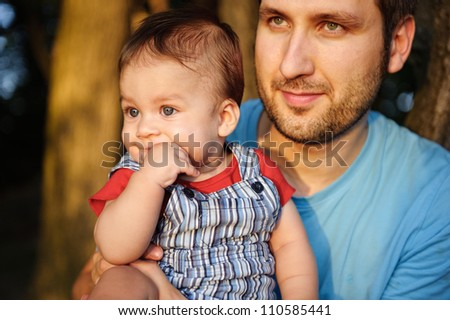 Father with his son in a park at sunset. - stock photo