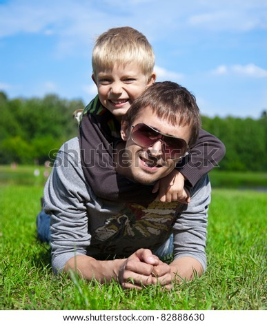 father with his son lying on the grass in the park, arm in arm - stock photo