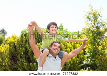 Father with his son playing in the garden - stock photo