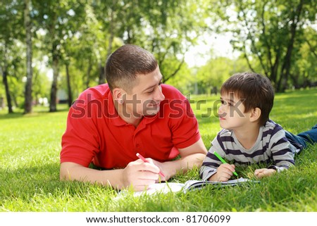 Father with his son reading together in the summer park