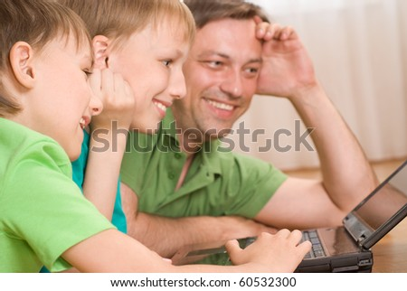 father with his sons is with laptop - stock photo