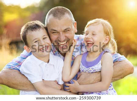 Father with his two children spending time together outside in green nature. - stock photo