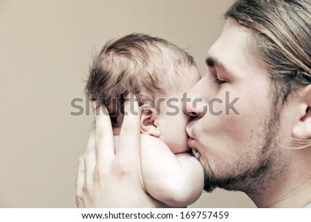 Father with his young baby cuddling and kissing him on cheek. Parenthood, love. - stock photo