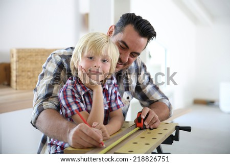 Father with kid measuring wood plank - stock photo