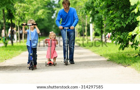 father with kids riding scooters in summer, family sport