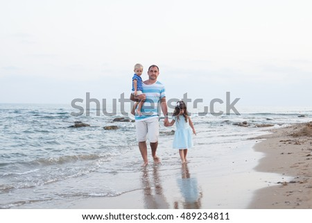 Father with kids walking along sand beach