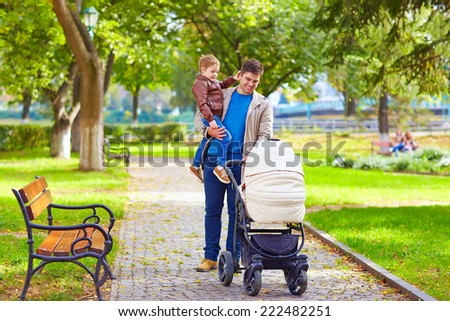 father with kids walking in city park - stock photo