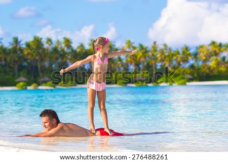 Father with little daughter at beach practicing surfing position - stock photo