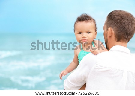Father with little daughter on beach