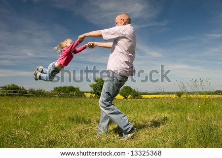 Father with little daughter playing in a meadow
