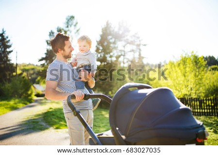 Father with little son and baby daughter in stroller. Sunny park